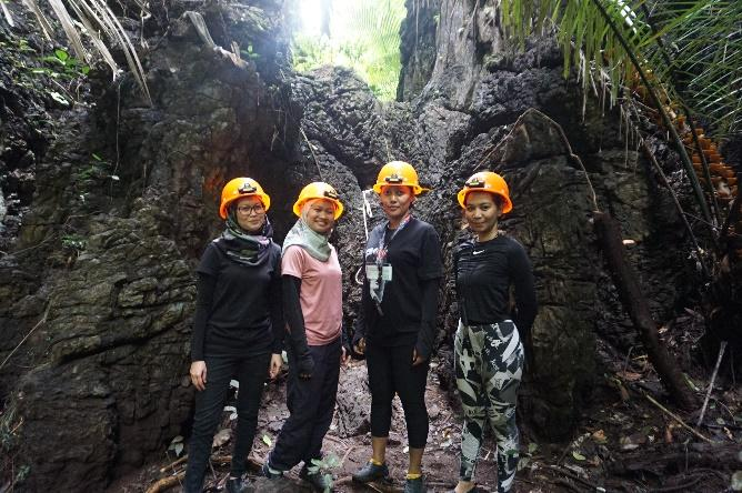 A group of people posing for a photo in a caveDescription automatically generated with medium confidence