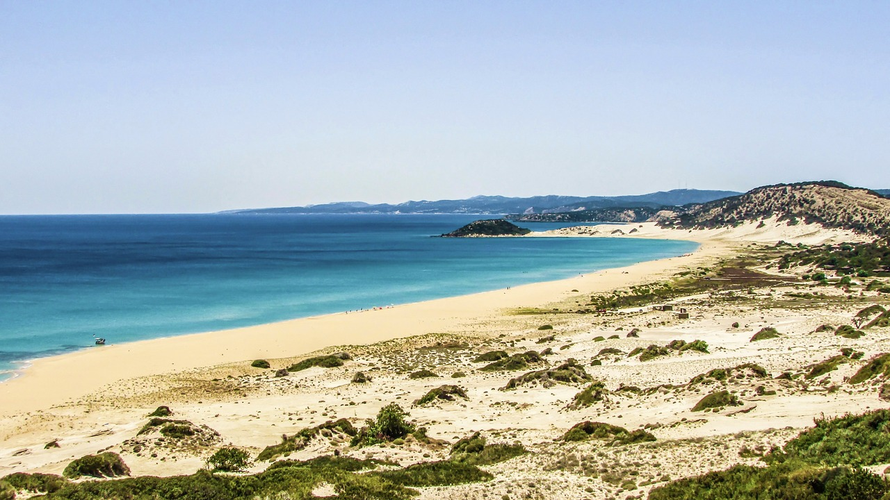 cyprus golden beach. empty sandy beach, long cove with calm blue sea and hills in distance. golden beach in cyprus is very underrated