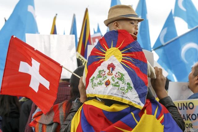 Ein Junge mit einer Tibetfahne und einer Schweizer Fahne sitzt auf den Schultern eines Mannes.