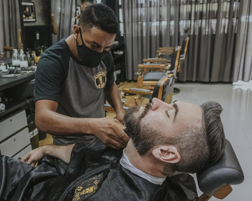man in black crew neck t-shirt cutting mans hair  patchy beard