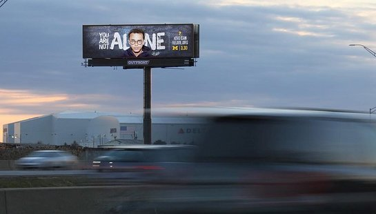 """Billboard of a teenager with glasses, and the text """"You are not alone"""" in white behind"""