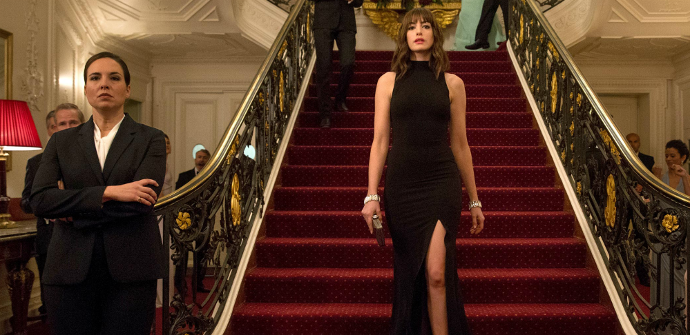 Two women are seen in an ornate room, a large staircase with an intricately detailed railing takes up much of the frame. Coming down the staircase is a woman in a long black dress (Anne Hathaway), to the left of her is a woman standing at the bottom of the staircase in matching business casual attire.
