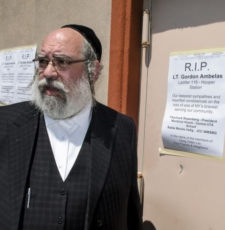 Rabbi Lieb Glantz from Central UTA passing posters with sympathy for the Fire Fighter Satmar synagogue is across the fire house where Ambelas was stationed.