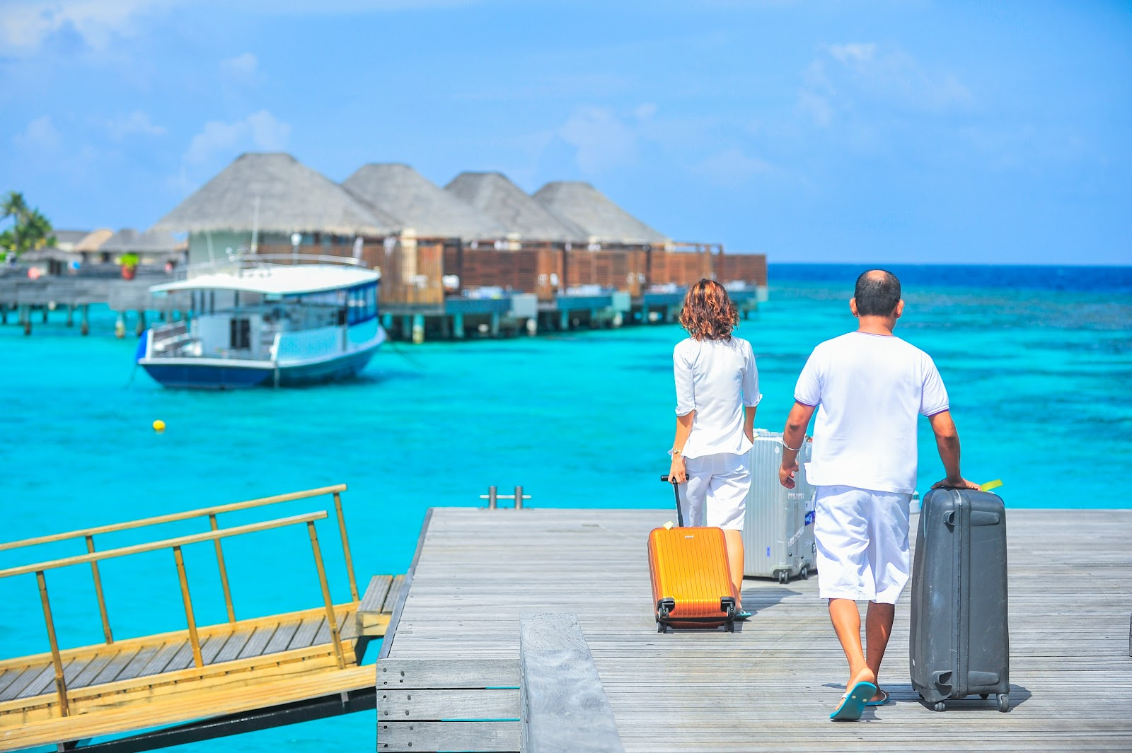 A couple with their bags arriving at the hotel on the beach