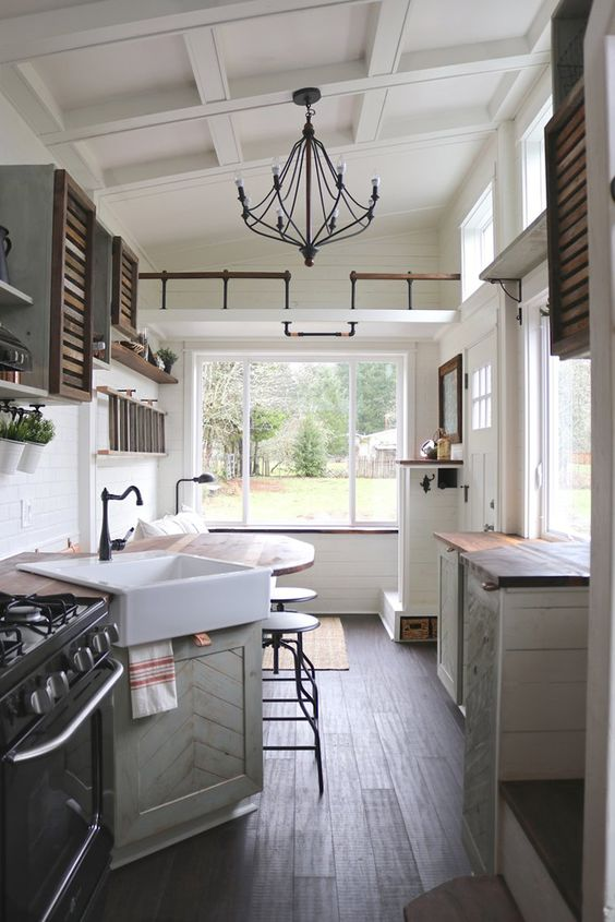 farmhouse tiny kitchen with grey cabinets, wood cabinets, wood floors, large window, barstools, tiny house kitchen decor, tiny home kitchen ideas