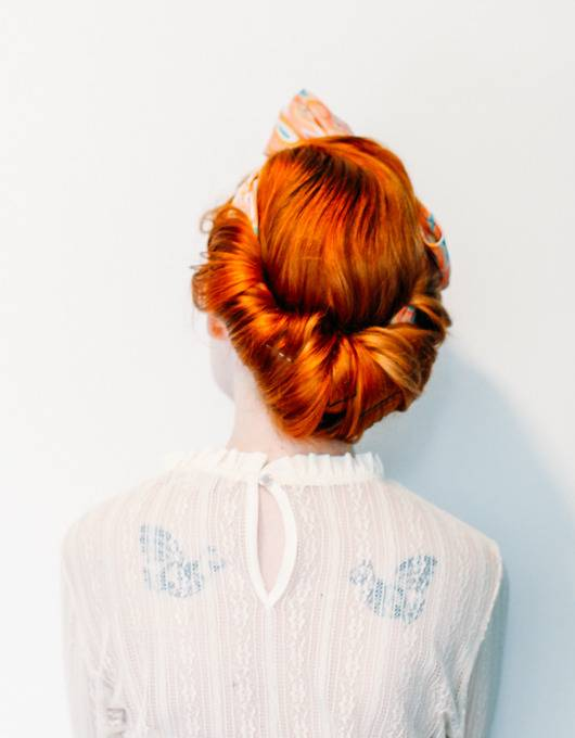 Red headed women wears her hair in a faux chignon, tied with a scarf