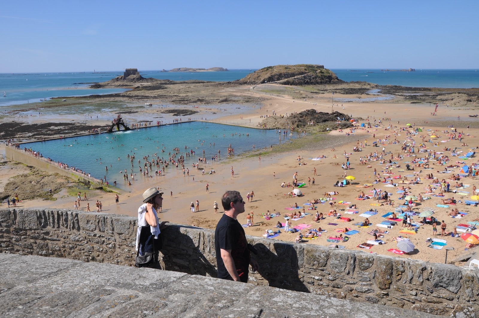 saint-milon plage du sillon public beach in france. Sandy beach filled with tourists, full swimming area and visitors sunbathing. Two tourists walking in foreground.