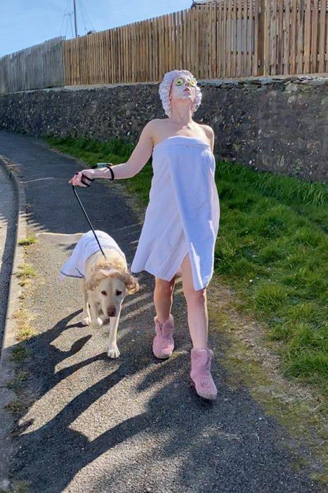 Mujer vestida con bata de baño mientras pasea con su perro