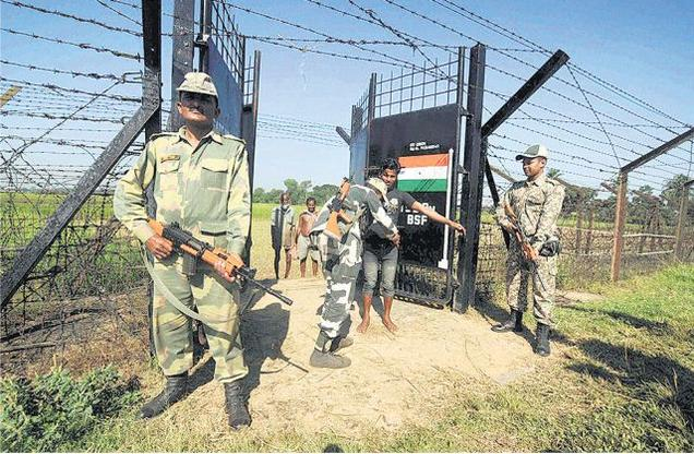 Border Security Force soldiers frisk farmers at the India-Bangladesh border in Lankamura village, on the outskirts of Agartala.