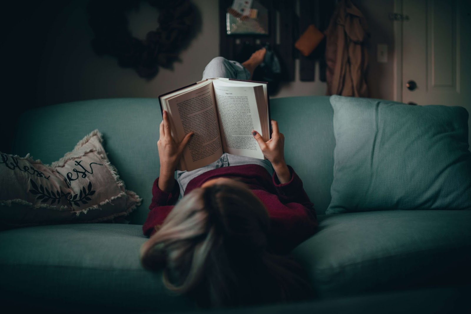 girl sitting on a blue couch reading a book