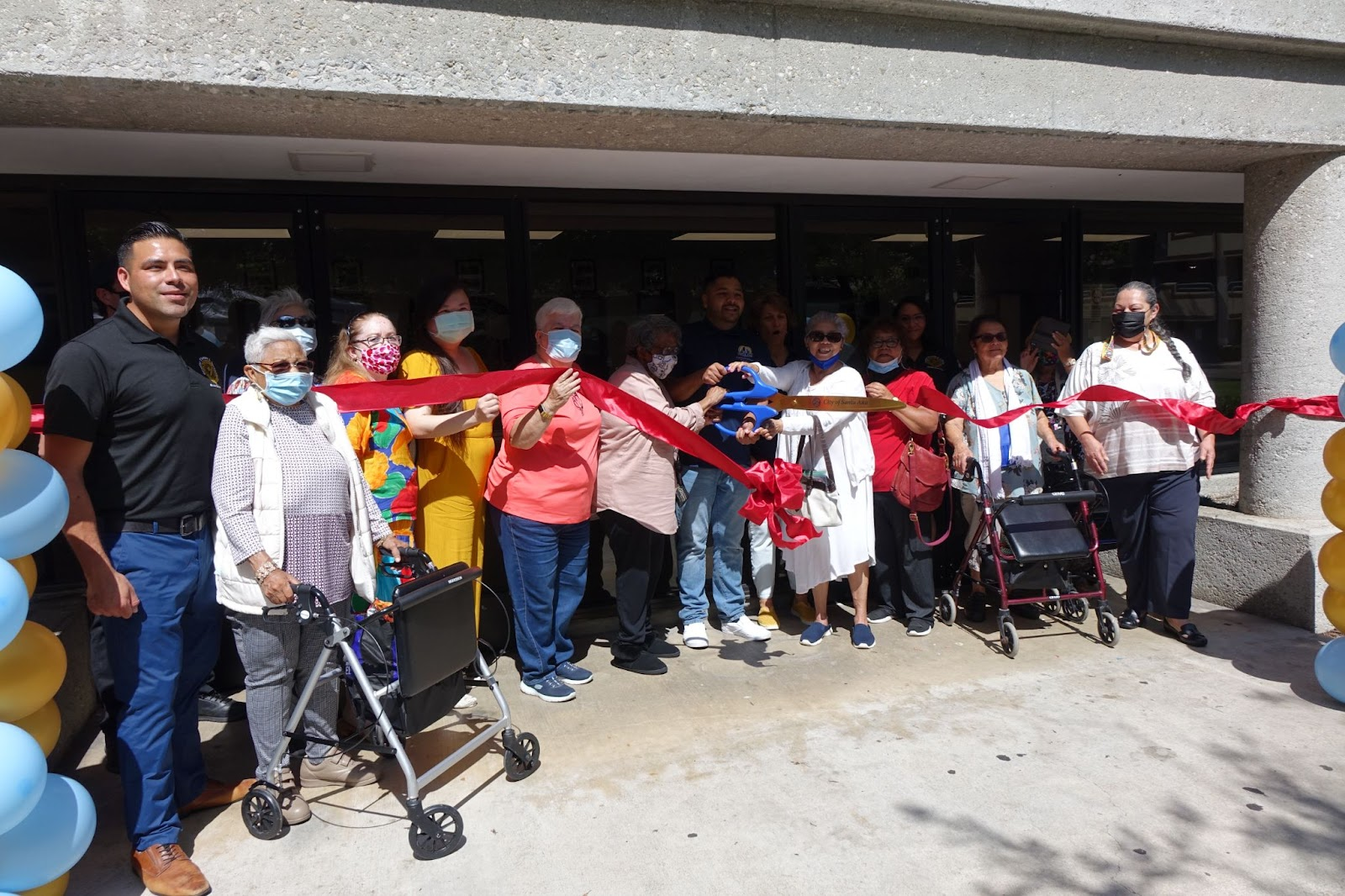 An image from the ribbon cutting at the Santa Ana senior center. There are about a dozen people in the photo, all but two are behind a red ribbon being cut and falling. Most everyone is wearing a mask and looking at the camera.