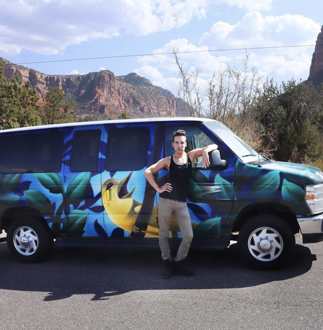 Justin Honard aka Alaska from RuPaul's Drag Race posing with his van