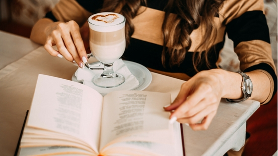 Woman reading a book with a festive drink on the table infront of her