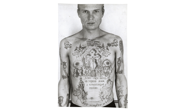 Череп и скрещенные кости на плечах заключённого указывают на то, что он отбывает пожизненный срок. А девочка, цепляющая платье удочкой на левом предплечье - наколка, которую обычно делают насильникам.