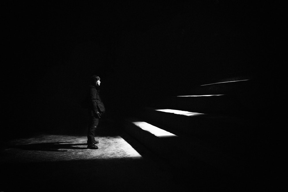 grayscale photo of man standing in front of stairs