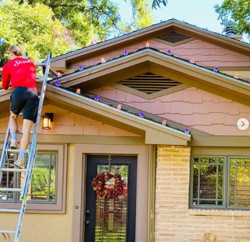 A dedicated Shine employee hanging up orange and purple Halloween lights around a satisfied client's house.