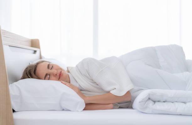 Beautiful young woman happy to sleeping in bed comfortably Beautiful young woman happy to sleeping in bed comfortably deeper sleep stock pictures, royalty-free photos & images
