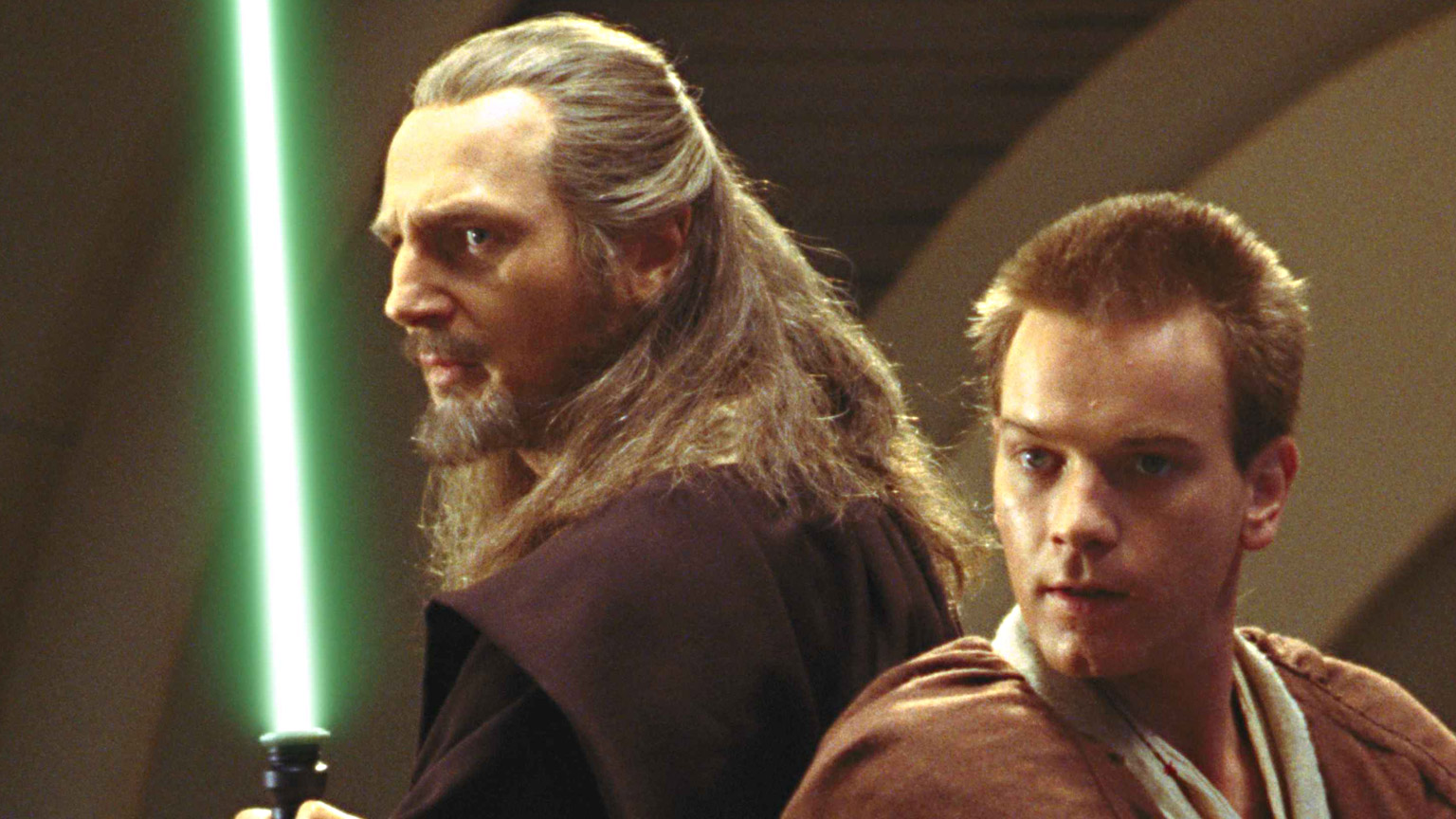 Qui-Gon Jin and Obi-Wan Kenobi standing back to back with lightsabers drawn.