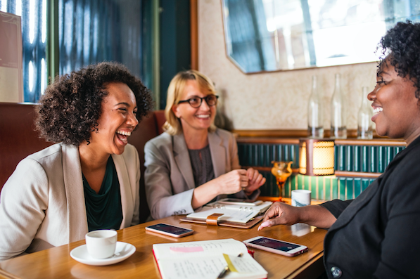 Three smiling women co-workers at a restaurant table