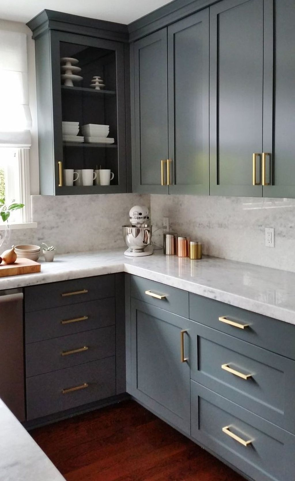 dark grey shaker cabinets with gold hardware pulls and marble countertops backsplash