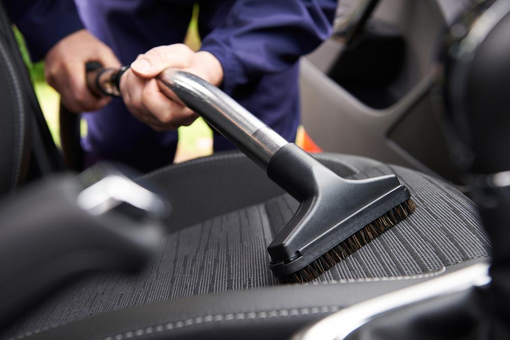Uma pessoa higienizando um banco do carro.