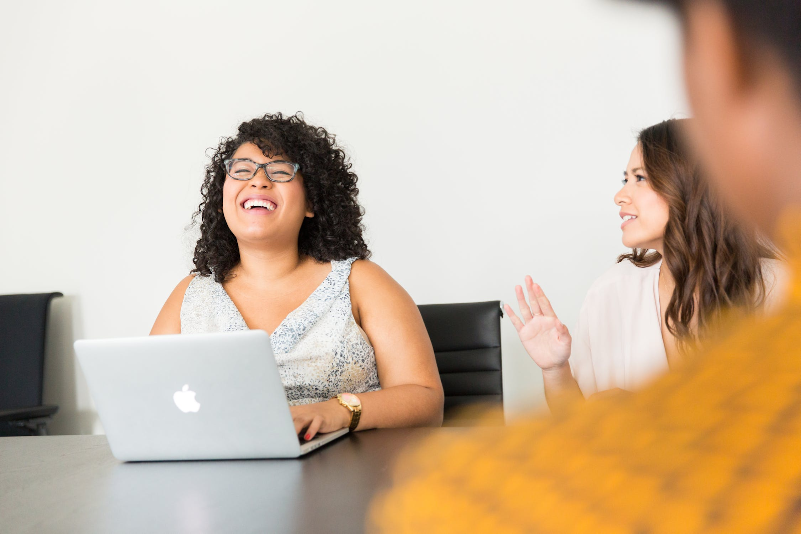 a woman on a laptop laughing at a coworker's joke