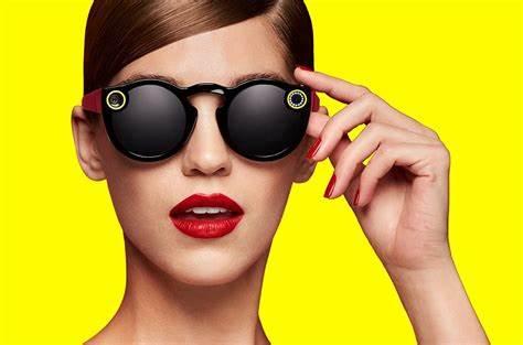 Gli Snapchat Spectacles hanno una forma tondeggiante, vetri scuri e le due fotocamere sono in vesta accanto alle lenti e sono rappresentate da due cerchi gialli.