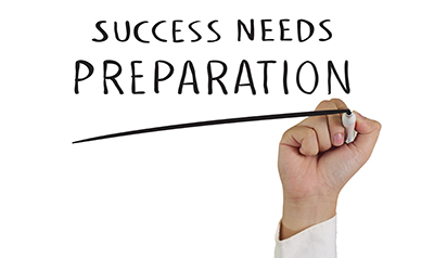 "A hand holding a white pen with the words, ""Success Needs Preparation"""