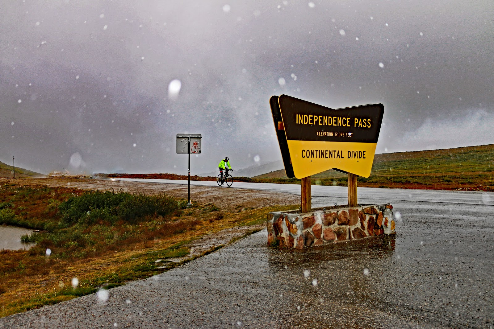 Bicycle ride up Independence Pass - Continental Divide sign and cyclist riding to it.