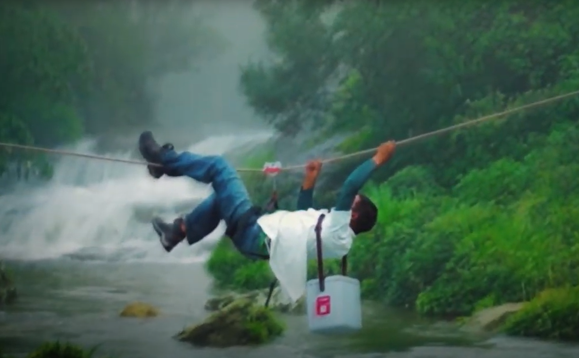 A man hangs from a rope as he carries vaccines over a river to reach a remote area.