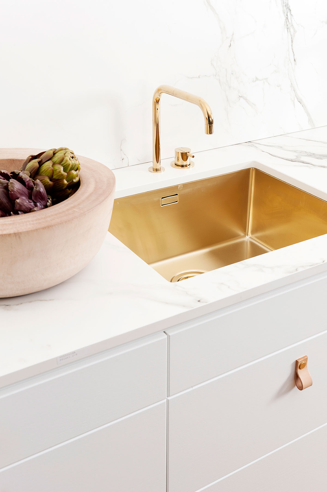 matte gold kitchen sink with gold faucet and white flat panel cabinets, surrounded by white marble countertop and backsplash