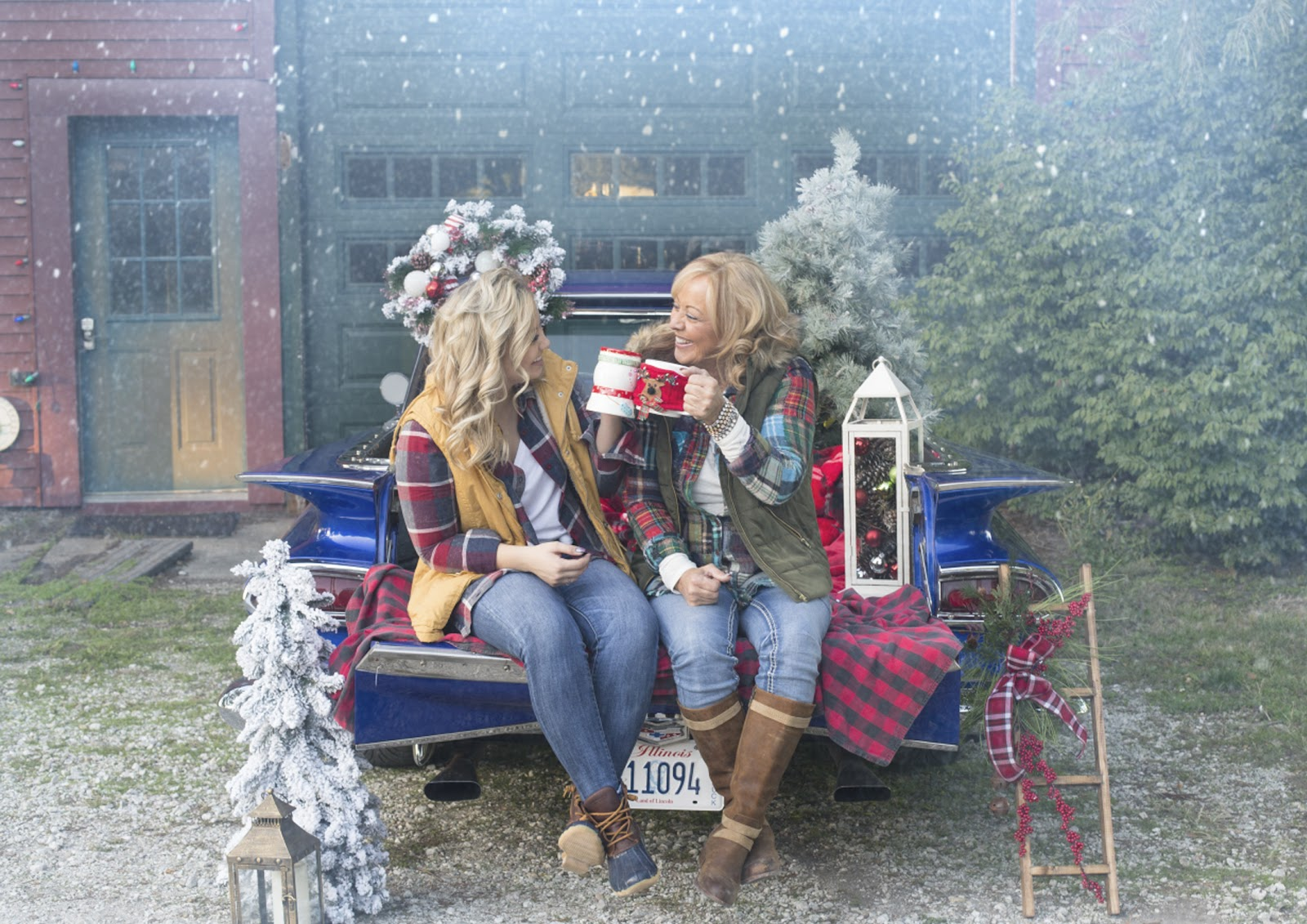 fun christmas card pose of two women sitting in the snow on a truck with hot chocolate at a christmas tree farm