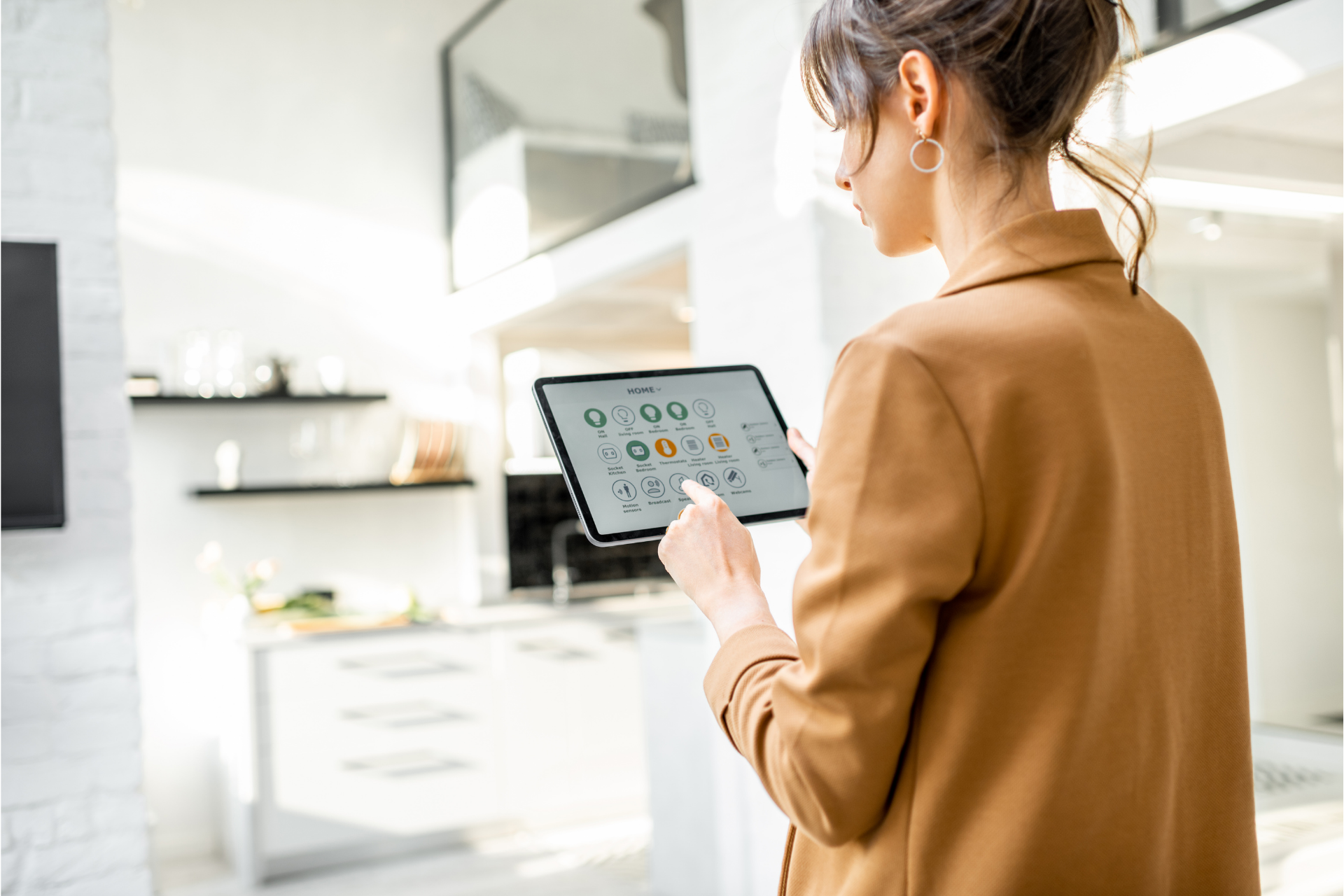 A woman uses a touch screen to operate her smart kitchen