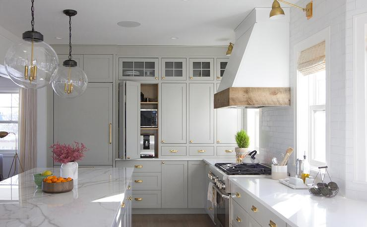 light grey shaker cabinets with white countertops and white range hood