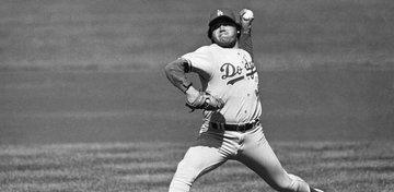 Foto en blanco y negro de un jugador de béisbol lanzando una pelota  Descripción generada automáticamente