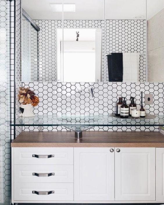 Banheiro em estilo minimalista com revestimentos das paredes de pastilhas hexagonais brancas., armário branco com bancada e cuba de vidro e espelho retangular por toda parede.