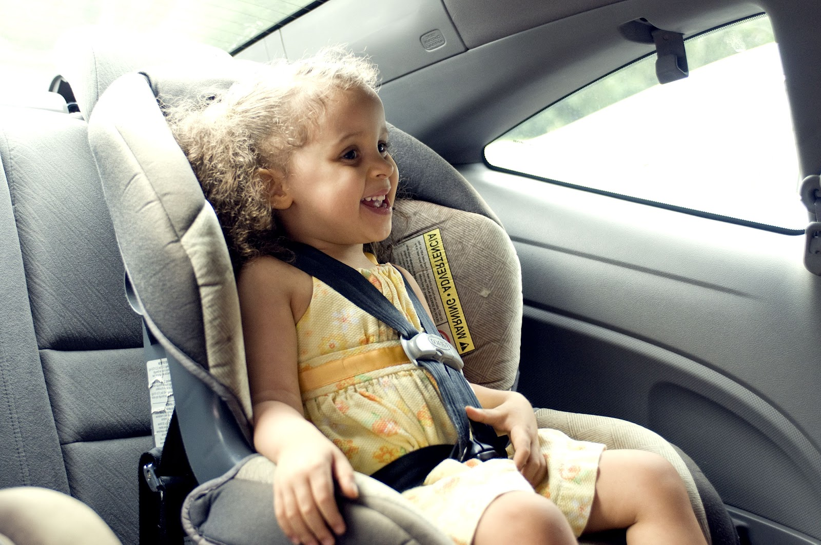 young-cute-female-child-in-back-seat-car-set.jpg