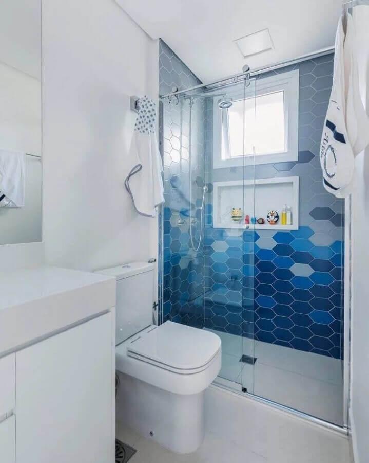 Banheiro com area do box revestida de azulejo hexagonal em tons de azul, piso branco e demais paredes pintadas de branco, armário e bancada da pia brancos e box de vidro