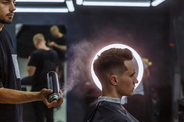 Barber makes hair styling with hair spray after haircut at the barber shop.