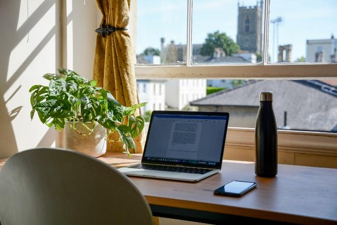 A picture containing table, indoor, window, computer  Description automatically generated