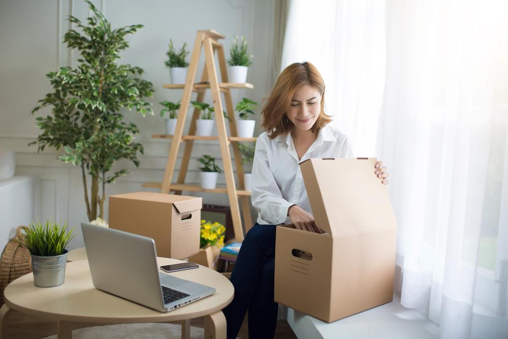 home, post, delivery and happiness concept - smiling young woman opening cardboard box at home,flare light
