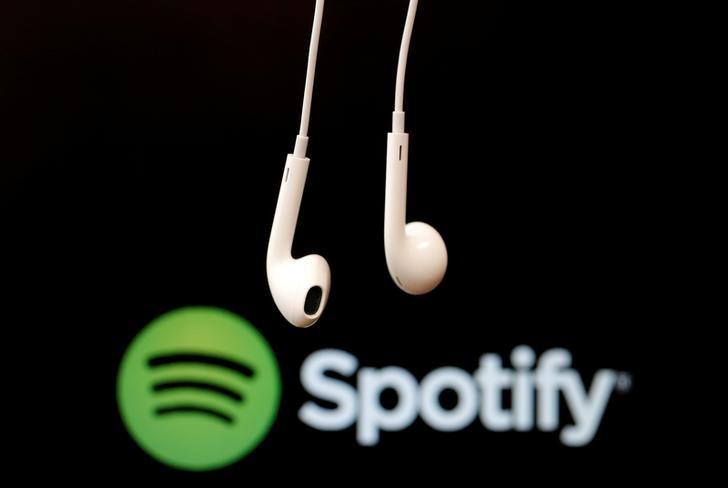 Fones de ouvido diante do logo do Spotify