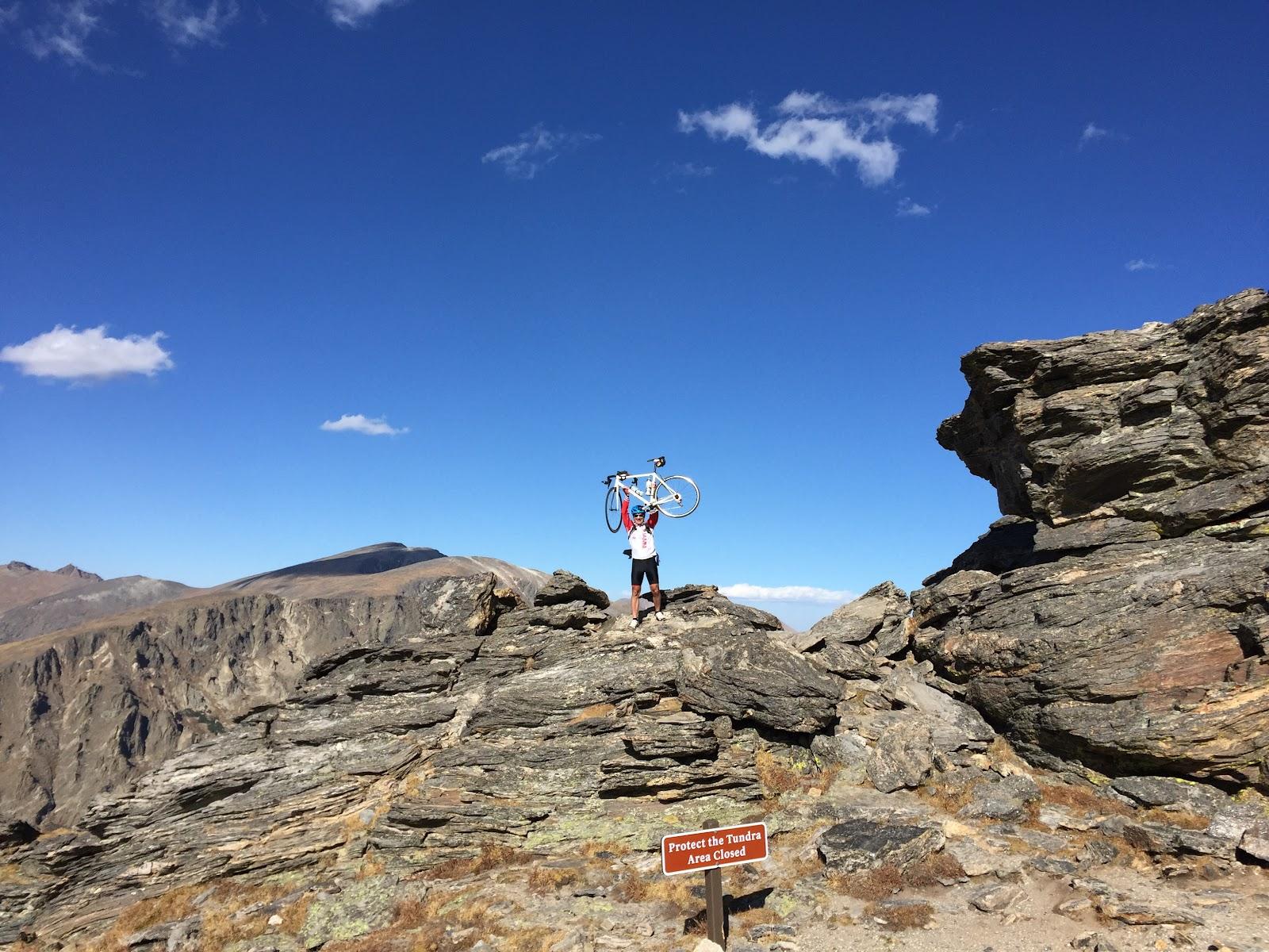 Cyclist holding bike over head at high point of Trail Ridge bike ridge Rocky Mountain National Park Colorado