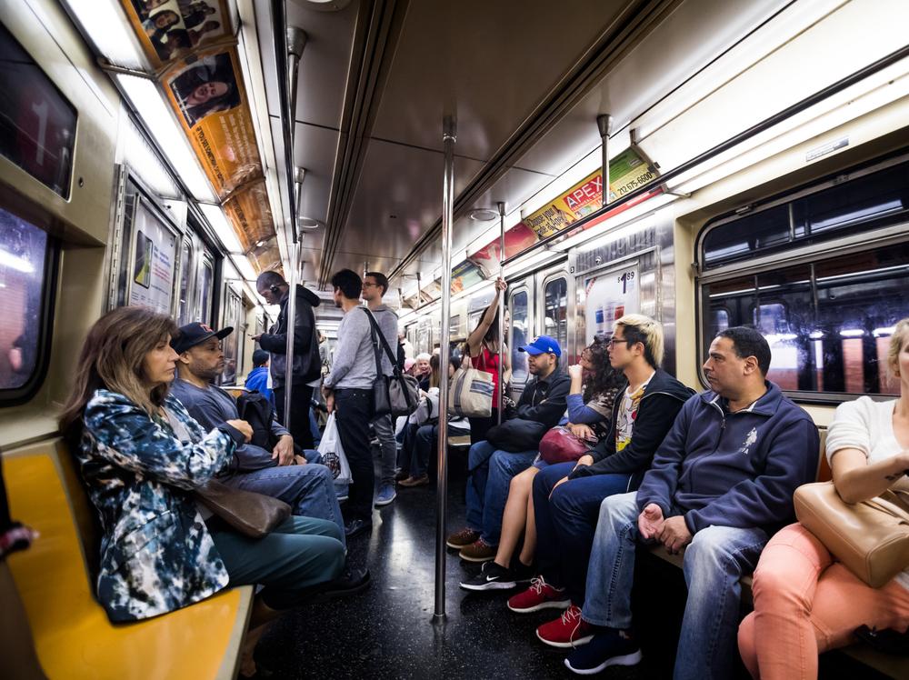 Pessoas dentro do metrô sentadas nos bancos e apoiadas nos postes