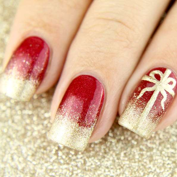 red nails with speckled gold tips & accent nail with golden present bow