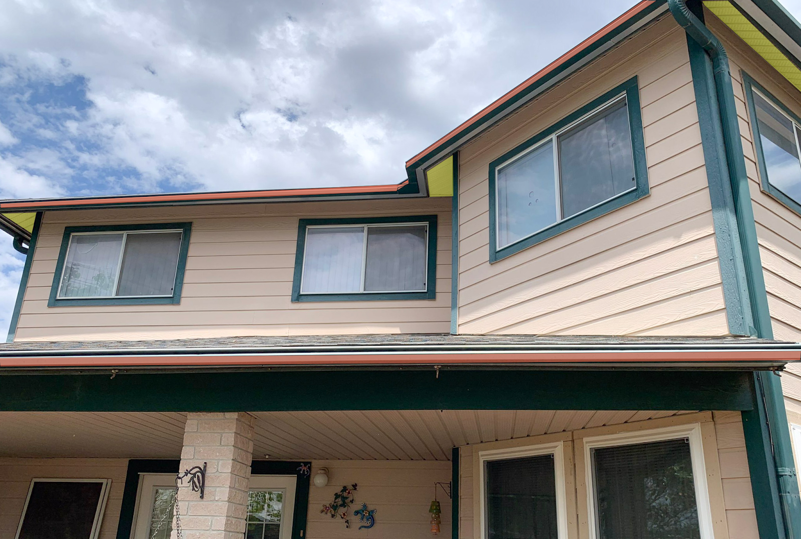 A picture of a house with the trim and underside of the roof is highlighted red and yellow to represent the soffit and the fascia.