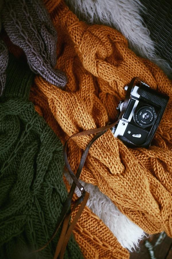 Foto de uma máquina fotográfica vintage em cima de uns casacos das cores verde escura e marrom
