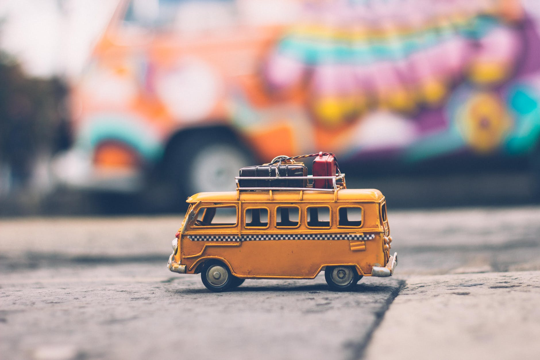 a toy yellow camper van with luggage on the roof rack.