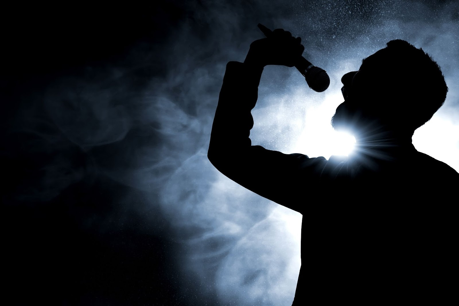 A silhouette of a man singing into a microphone