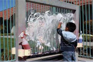 A child spreading shaving cream on a transparent easel